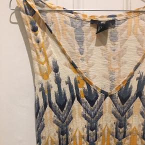 Maxikjole i blå/gul/hvid og i flot mønster. Kjolen har brede stropper og udskæring. Den har et smalt bindebånd midt på.