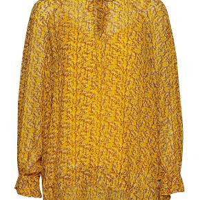 Super fin bluse med lange ærmer i gul med brunt branch print. Blusen har v-udskæring med bindebånd øverst. Blusen har også fine flæser for enden af ærmerne.  100% viskose