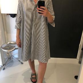 Skjorte kjole. Fremstår uden brugsspor. Sort og hvid stribet. A-snit med lommer og knapper ved halslukning.