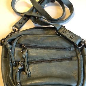 Fin taske i skind med mange detaljer, 3 mindre rum foran, indeni er der 1 lynlåsrum og 3 andre små rum. Farven er nærmest army-grå-agtig. Bytter ikke