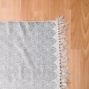 Langt blå- og hvidmønstret gulvtæppe sælges.   Mål: ca. 65 cm (B) x 182 cm (L)