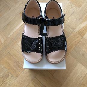 Varetype: Sandaler Farve: Sort  Super fin sort lak sandal (smal læst) med velcro. Aldrig brugt. Indvendigt mål 21,5 cm. Købes som beset på billede. Pris forudsætter MobilPay og tillægges porto.