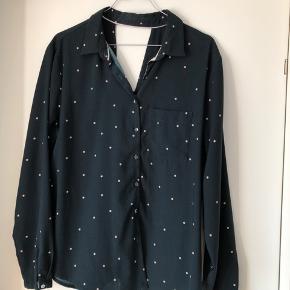 Mørkeblå skjorte med lyserøde prikker og åbning i nakken. Knapperne er lidt slidte, men ellers fejler den intet.