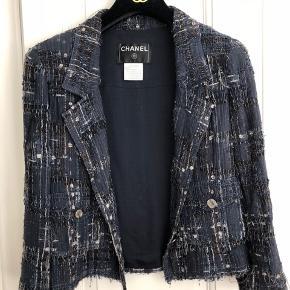 Klassisk jakke fra Chanel (Fr str 36) fra forårskollektionen 2006. Grundfarven er blå med boucle stof i både sort, hvid og brun. Med silkefoer og kæde forneden.