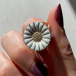 Georg Jensen Daisy/margueritring sælges, da jeg ikke får den brugt. Diameter på blomst: 1,8 cm. Mener det en str. 54, men er ikke 100% sikker. Har ikke mulighed for at få det tjekket lige nu, men ringer måler 1,8 cm i diameter. Forgyldt sølv. Der er en meget lille skade på emaljen, men det er så småt, at jeg ikke kan fange det med kameraet. Original æske medfølger.   Bytter ikke. Ønskes TS-handel betaler køber gebyrerne.