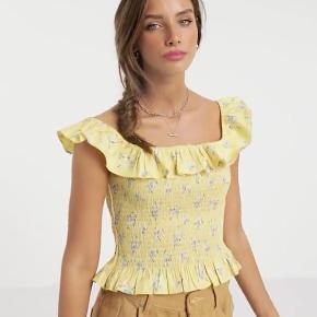 Fin gul top med blomster-mønster og firkantet halsudskæring. Har de fineste flæse -detaljer. Brugt 1 gang