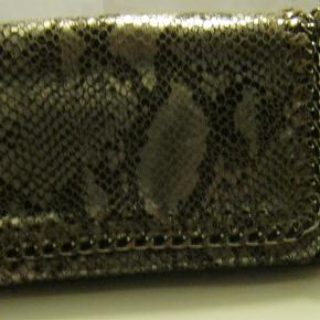 Fin lille skindtaske fra Fonnesberg. Skindet har et slangeskindpræg m. sølvskin og lang kædehank, så den kan bruges som cross-over. Tasken lukkes med magnetlukning og har lynlåslukning + indvendigt lynlåsrum. Hanken kan tages af, så den også kan bruges som en Clutch. Er som ny, da den er kun brugt en gang.  Str. : længde 23 cm, højde 14 cm, bredde i bunden 8 cm.   Materiale: Genuine Leather + kædehank i sølv m. skindindsats  Priside: 400 kr. PP  IKKE BYTTE  Fonnesberg - lille fin skindtaske med lang kædehank Farve: skind m. slangeskindpræg Oprindelig købspris: 1399 kr. Kvittering haves