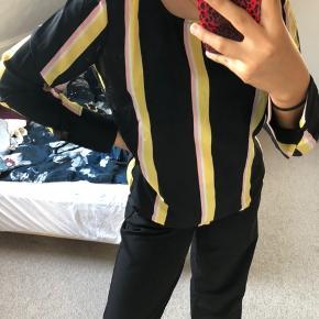 Fin bluse i sort med gule/lyserøde/hvide lodrette striber, med knap i ryggen