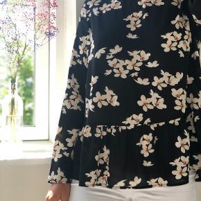 Sort Envii skjorte med hvide og gule blomster. Skjorten har en peplum kant.  Info: -Fra røg- og dyrefrit hjem -Køber betaler selv porto