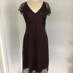 Smuk kjole i mørkebrun fra Fransa. Korte ærmer, som er gennemsigtige. Mørkebrun underkjole med et gennemsigtigt lag udenpå, som er fyldt med fine blomster med glimmer. Bindebånd, som kan bindes foran eller bagpå. Lukkes med skjult lynlås i venstre side. Længde fra skulder er 114 cm, brystmålet er 94 cm, og taljen måler 81 cm. Fremstillet af polyester. Bærer ikke præg af brug.