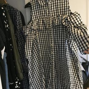 Kjolen er brugt en enkelt gang, og fremstår derfor som ny, og en smule krøllet da den har ligget foldet sammen :-) Kjolen er sort/grå/hvid gingham tern og med 'cold-shoulders'.
