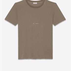 Varetype: Khaki Logo T shirt Farve: Armygrøn Oprindelig købspris: 2600 kr. Kvittering haves. Prisen angivet er inklusiv forsendelse.  Khaki signature logo t-shirt fra Saint Laurent   Størrelse XS. Fitter relaxed i størrelsen. Perfekt til en strørrelse Small. Saint Laurent logo på maven.   Super lækker og luksuriøst i materialet. Perfekt til skinny jeans. Fremstår i perfekt stand.  Købt i Paris og sælges i perfekt købt stand med original tag samt kopi af kvittering.   Nypris 2.600kr Sælges for 1.800kr inkl forsendelse.