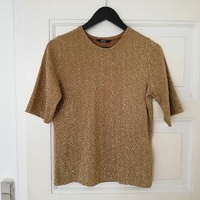 Flot guld t-shirt med glimmer, lidt lille i størrelsen. Med lidt længere ærmer.