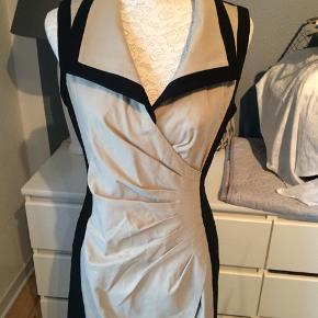 Kjolen er i farverne sort og sand. Helt ny og ubrugt. 74% rayon og 23% nylon og 3% elastin.