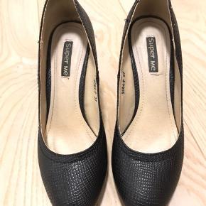 Lækker sort stilet med slangeskindsmønster. Er for bred til min fod, så er brugt 3 gange.  Hælhøjde er 9 cm.