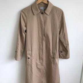 Lang oversize trenchcoat fra H&M. Enkeltradet med skjulte knapper og aftageligt bælte med guldspænde. Lang slids bagpå. Blanding af polyester og bomuld. Har et tyndt foer.