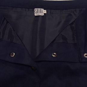 Kort nederdel med knaplukning ned foran. Skrålommer og foer. Det ligner ruskind, men er det ikke