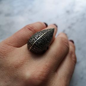 Flot ring i sølvbelægning og sorte sten. Str. M. Belægningen er lidt slidt, men mest bagpå. Ingen sten mangler.