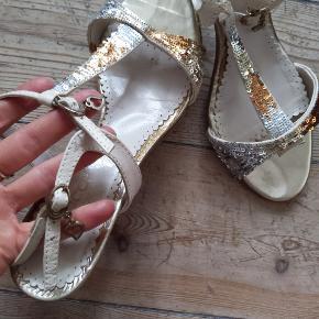 Sandaler/stilletter fra Bianco i str. 39 med pallietter. De er brugte men slitagen ses næsten udelukkende på indersålen. Resten er velholdt.   De er super fine og nemme at gå med.  Hælen måler 8 cm.  Det er muligt at mødes og prøve dem på.