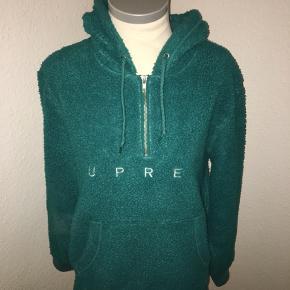Grøn hoodie / hættetrøje fra supreme i teddy stof med half zip med Hvidt supreme logo på fronten. Størrelsen er en stor small.