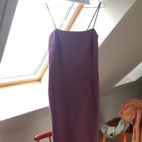 Smuk figursyet kjole med spaghetti-stropper og slids i venstre side. 54% polyester, 44% uld og 2% elasthane.