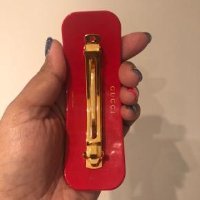 Rødt spænde med grønne og klare  krystaller.  120/45 mm. Har været prøvet på 1 gang. Sælges også i brun med krystaller.