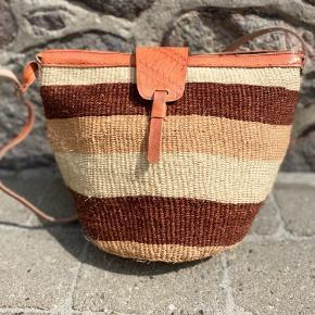 Smuk, håndlavet sisaltaske med detaljer af ægte læder. Læderremmen kan justeres til den ønskede længde. Åbningen på tasken er ca. 35 cm. Den er foret indvendigt og der er lynlås i toppen.   Se flere tasker på min profil i forskellige designs og størrelse.   Taskerne er købt på lokale markeder i Kenya.  Varen kan sendes med DAO eller afhentes efter aftale.   # Crossbody taske, Afrika, Kenya, sisal, unik