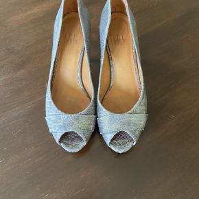 Brugt 1 gange. De fremstår stort set som nye. Er desværre for høje til mig. Hælhøjde 8 cm. Farven er grå metallic med et strejf af bronze.